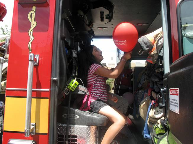 Marina Avila plays inside a fire truck with a Crime Stoppers balloon she got from a Metro Police officer Saturday at a block party and safety fair sponsored by Metro in downtown Las Vegas.
