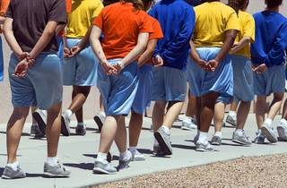 Juveniles hold their hands behind their backs as they walk through the Clark County Juvenile Detention Center on Wednesday, May 25, 2011.