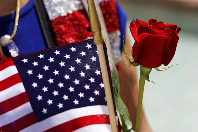 Anita Gargus holds a rose and an American flag before participating in a Special Forces Ceremony at the Southern Nevada Veterans Memorial Cemetery in Boulder City Sunday, May 29, 2011.