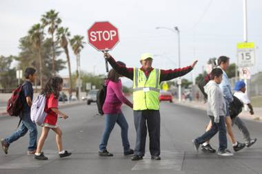 Crossing Guard, Francisco Esteban, stops traffic allowing children to safely cross the street in front of McCall Elementary School in North Las Vegas Wednesday, June 1, 2011.