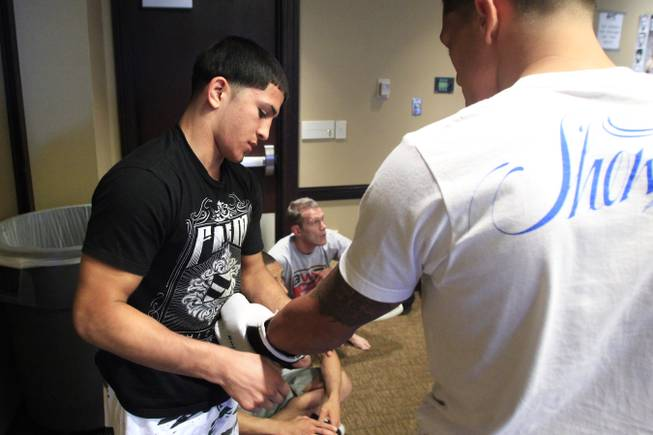 Sergio Pettis helps put on his brother Anthony Pettis' gloves during workouts for the TUF Season 13 fight card Thursday, June 2, 2011.