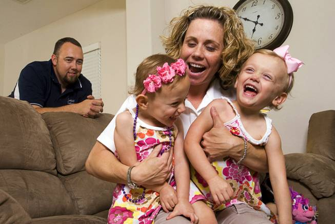 Geoff Walker, an English teacher and assistant football coach at Foothill High School, looks on as his wife, Shelby Walker, a geography teacher at Mannion Middle School, plays with twins Colbie, left, and Kenna, 3, at their home in Henderson on Thursday, June 2, 2011.