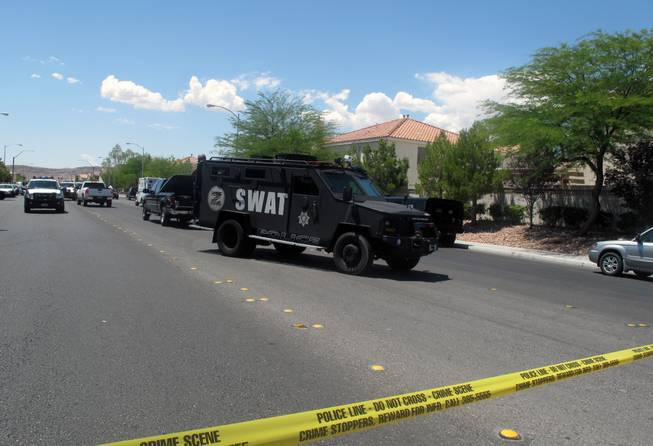 A Metro Police SWAT vehicle prepares to leave the southwest valley neighborhood where a man barricaded himself in a stranger's home while evading arrest. SWAT negotiators later convinced the man to surrender.