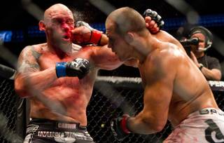 Junior Dos Santos, right, of Brazil, hits Shane Carwin, of Greeley, Colo., during their main event heavyweight mixed martial arts bout at UFC 131, Saturday, June 11, 2011, in Vancouver, British Columbia. Dos Santos won by decision.