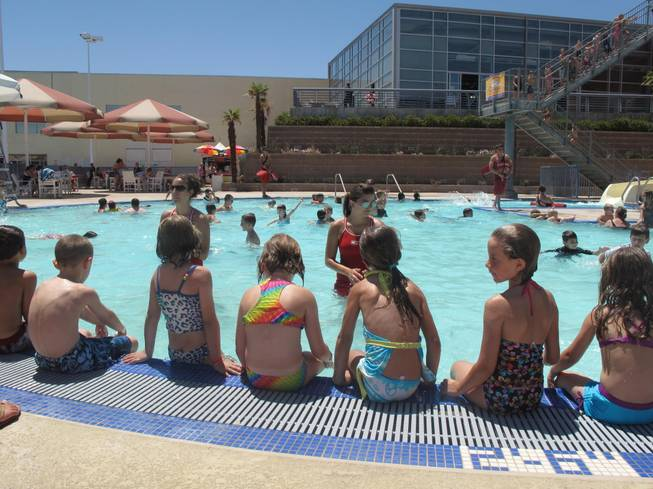 Children at the Henderson Multigenerational Center pool listen to lifeguards as they prepare to start their swim lesson Tuesday morning. The swimmers were part of an international attempt to break the record for the world's largest swim lesson.