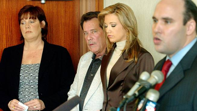Former Miss Nevada USA Katie Rees, second from right, dethroned over raunchy photos posted online, listens to her attorney Mario E. Torres III, right, during a press conference while flanked by her parents, Shannon and David Rees, in Clearwater, Fla., Saturday, Dec. 23, 2006.
