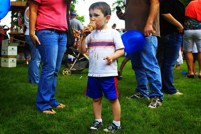 A young boy enjoys an ice cream cone during Party in the Park in Charles City, Iowa.