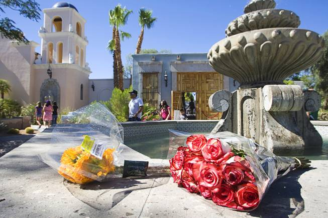 Flowers are left by a fountain outside a home where entertainer Michael Jackson used to live on Palomino Lane Saturday, June 25, 2011. The homeowner opened a portion of the home to the public to mark the second anniversary of the entertainer's death.