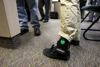 A juvenile offender is shown after being outfitted with a SecureAlert GPS ankle-bracelet in a courtroom at the Family Court building Thursday, June 30, 2011.