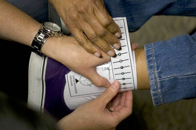 Probation officers take a measurement before outfitting a juvenile offender with a new SecureAlert GPS ankle-bracelet in a courtroom at the Family Court building Thursday, June 30, 2011.