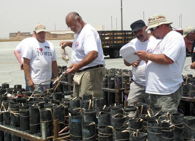 "Pyrotechnicians confer about the setup of fireworks for the next day's launch at Texas Station. The fireworks will be part of Station Casinos' ""35th Anniversary, 4th of July Blast"" at five of its properties in the Las Vegas Valley."