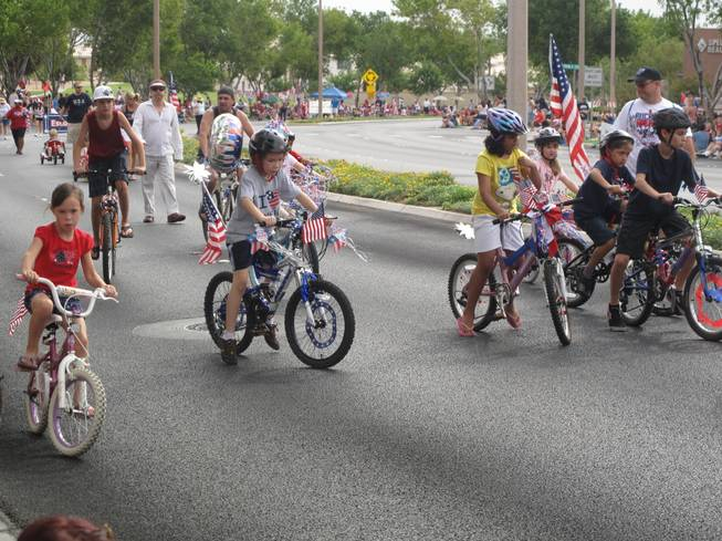 A group of children riding bikes and scooters adorned with American flags help kick off Summerlin's 17th annual Patriotic Parade as part of the parade's escort division.