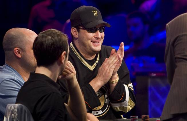 Phil Hellmuth Jr., center, competes at the final table of the $50,000 buy-in, Poker Player's Championship during the World Series of Poker at the Rio Wednesday, July 6, 2011.
