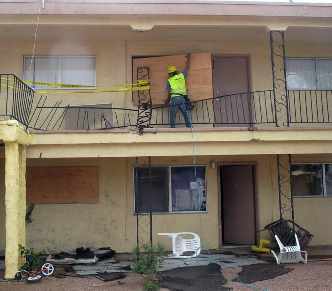 Crews board a window shattered by a metal railing Sunday afternoon at the Willow Gardens apartment complex on Vegas Drive. Heavy rain and strong winds slammed the railing into the apartment unit.