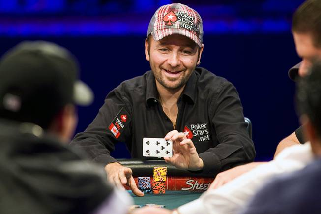 Poker professional Daniel Negreanu of Canada shows his card to an opponent after winning a hand during the World Series of Poker main event at the Rio Monday, July 11, 2011.