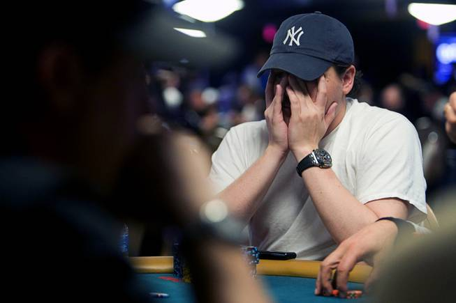 Poker professional Shaun Deeb rubs his face during the World Series of Poker main event at the Rio Monday, July 11, 2011.