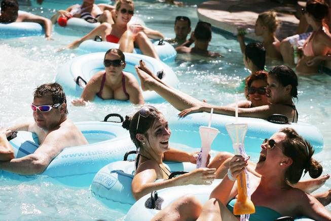 Guests enjoy drinks while floating down the MGM Grand pool's Backlot Lazy River in Las Vegas Monday, July 11, 2011.