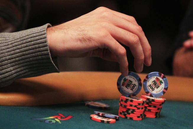 A competitor plays with his chips during play at the 2011 World Series of Poker Friday, July 15, 2011.