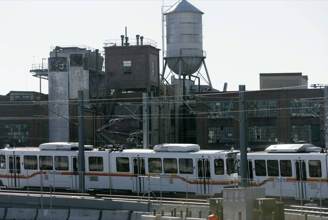 Headed south toward Denver's burgeoning suburbs, a Regional Transportation District light rail train passes in the shadow of the empty Gates Rubber Company plant in south Denver on Sunday, Nov. 19, 2006.