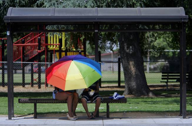 A couple of public transit riders take shelter from the heat under an umbrella at a bus stop Thursday, May 18, 2006, in Fresno, Calif.