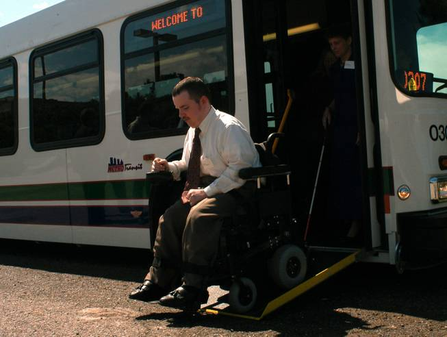 Jason Parker leaves one of the new wheelchair-accessible Metro Transit buses Tuesday, June 3, 2003, after a press conference outside the State Capitol in Oklahoma City, dealing with access for the disabled to public transportation.