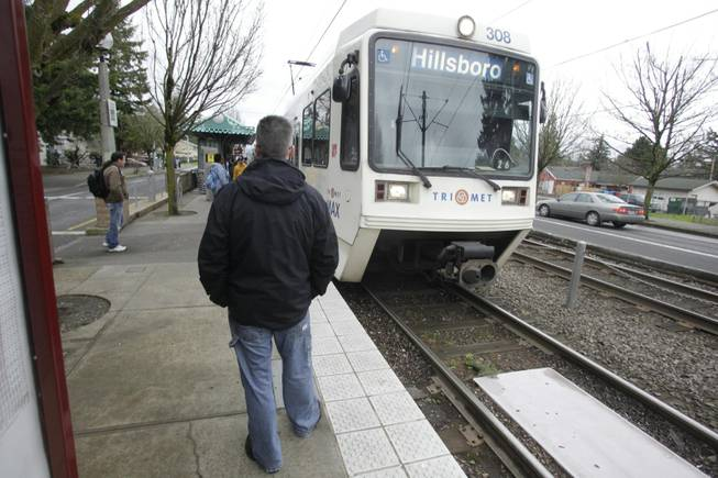 Scott Nielsen waits for a train at the TriMet light rail stop at 162nd Avenue Wednesday, March 30, 2011, in Portland, Ore.
