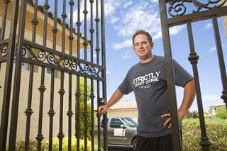 Steve Antill opens a security gate he built for a homeowner in Southern Highlands Monday, July 18, 2011. Antill, owner of Strictly Iron, started his business about a year ago after being laid off from the ornamental ironwork company where he was an employee.