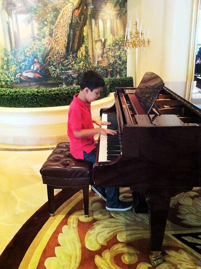 Ethan Bortnick, a 10-year-old piano prodigy, will perform this weekend at the Hilton, making him the youngest entertainer to headline a show in Las Vegas. In this photo, he plays piano in a VIP suite at the Hilton.