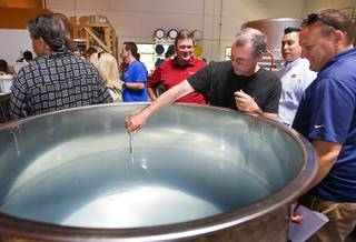 Las Vegas resident Tony Moore checks a alcohol measurement gauge in a vat of 7 grain Las Vegas Whiskey during the official grand opening of the Las Vegas Distillery in Henderson Friday, July 22, 2011. The whiskey will acquire a darker color after it has been aged in barrels.