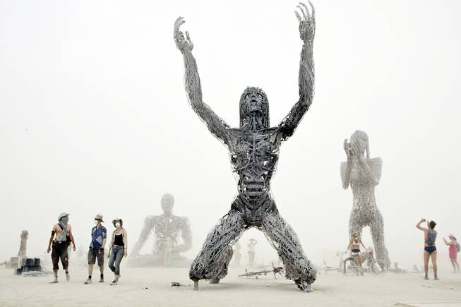 "In the midst of a white-out dust storm, Burners visit ""Crude Awakening"", a multi-artist structure at Burning Man in 2007."