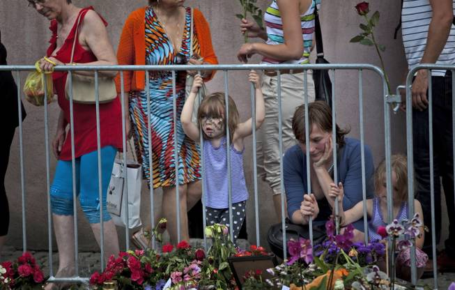 People look at tributes outside the Oslo Cathedral in Oslo, in memory of the victims of Friday's bomb attack and shooting rampage, Norway, Thursday, July 28, 2011.