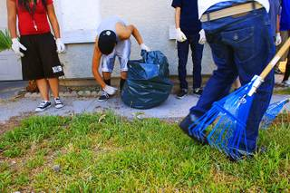 Youth offenders clean up the yard of a foreclosed home Thursday, July 28, 2011.