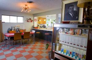 "The dining room is shown in the home of Courtney Mooney and Josh Rogers Sunday, July 31, 2011. At right is an old cigarette  vending machine. At top right is a portrait of Jack Cortez who used to publish ""Fabulous Las Vegas,"" a weekly magazine promoting events, entertainment and activities in Las Vegas. The magazine was published from the late 1940s to the early '70s although Jack Cortez died in 1967."