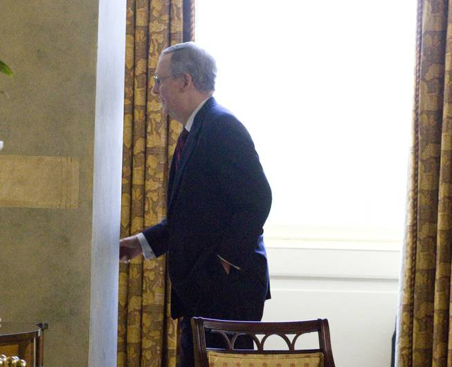 Senate Minority Leader Mitch McConnell enters his office on Capitol Hill in Washington, on Sunday, July 31, 2011.