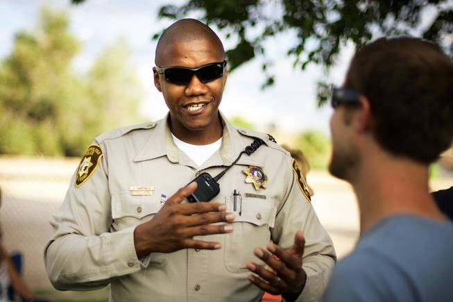 Metro Officer Charleston Hartfield talks with a community member during National Night Out at Molasky Family Park in Las Vegas, Tuesday, Aug. 2, 2011. Hartfield was one of the people killed when a gunman opened fire at a country music festival in Las Vegas on Sunday, Oct. 1, 2017.