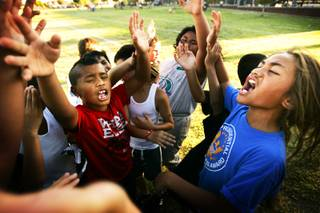 Members of the Island Warriors team cheer after a drill at football practice at Liberty High School in Henderson Thursday, August 4, 2011.