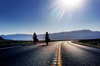 Norwegians Frida Devold and Gunnvor Ness ride their bikes on Highway 50 east of Eureka on Tuesday, Aug. 9, 2011.