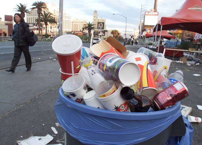 A pedestrian walks past a can full of garbage on the Strip.
