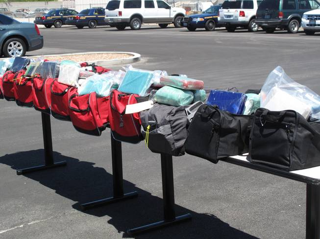 Authorities display bundles of cocaine that were seized from 10 duffel bags during a bust Aug. 10 on Interstate 15.