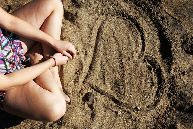 Angela Meidaa of Los Angeles admires a heart she drew on the beach  near Zephyr Cove on the Nevada side of Lake Tahoe Wednesday, August 10, 2011.
