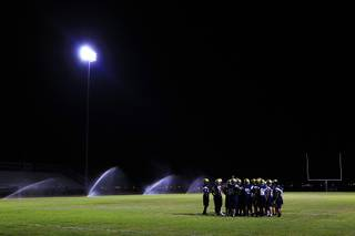 Spring Valley players huddle during their annual midnight football practice to kick off the season Thursday, August 11, 2011.