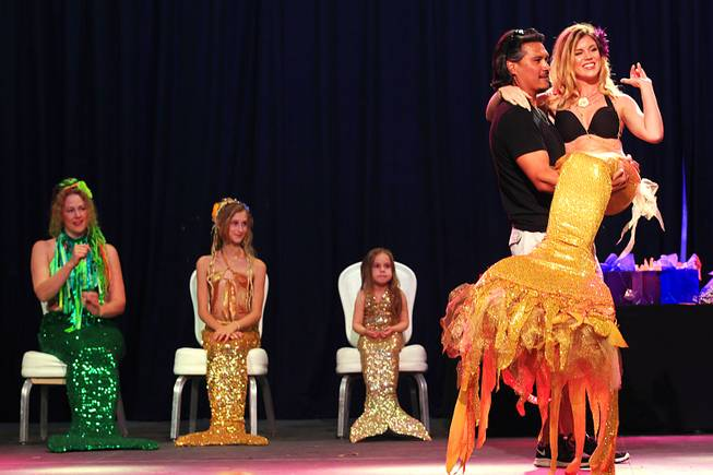 Juliana Tucker is carried onstage by Joe Davila during the first International Mermaid Pageant held as part of MerCon 2011 at Silverton Casino Lodge on Friday, Aug. 12, 2011.