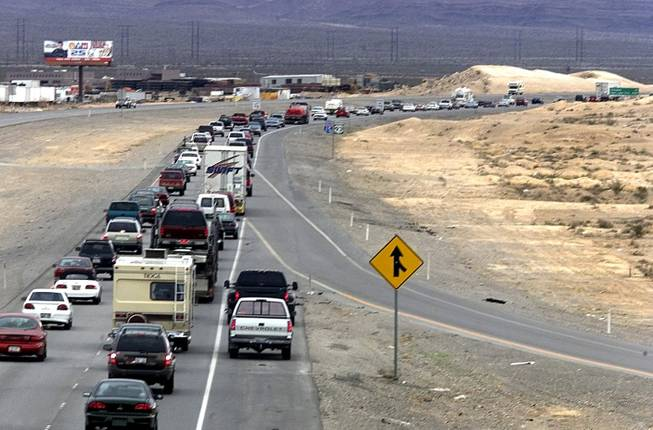 A pair of trucks pass illegally on the right shoulder as race fans jam Interstate 15 near Lamb Boulevard as they head to the CarsDirect.com NASCAR race at the Las Vegas Motor Speedway Sunday, March 5, 2000. This photo was taken at 10:45 a.m., just 45 minutes from the scheduled start time.