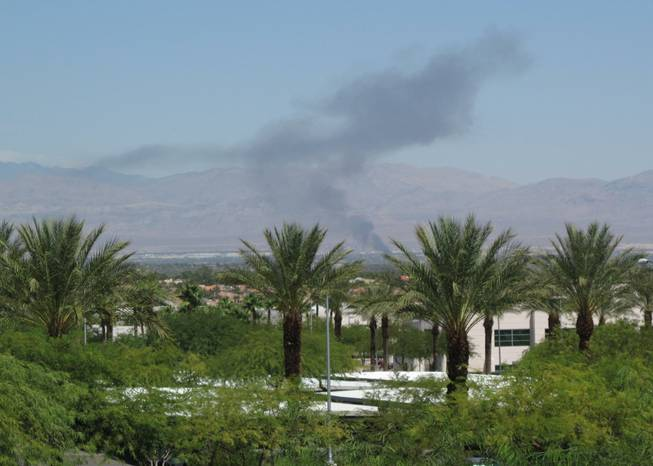 Smoke is visible across the Las Vegas Valley on Wednesday as fire damaged a shed and vehicles in the northeast valley.