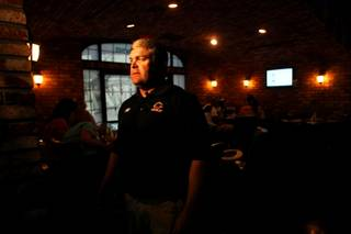 First-year Chaparral football coach, Bill Froman, is interviewed during a fundraiser hosted by the school's alumni association at Murphy's Law Pub and Grill in Las Vegas Saturday, August 20, 2011. The money raised is to update equipment and help the new coach turn the program around.