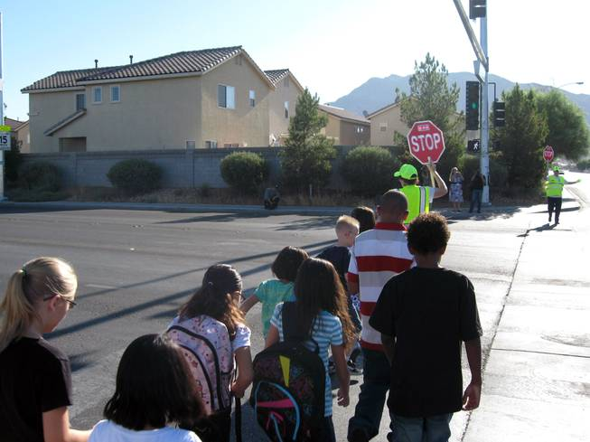 Children follow crossing guard Marylyn Thorn across Christy Lane near Richard Rundle Elementary School on Tuesday.