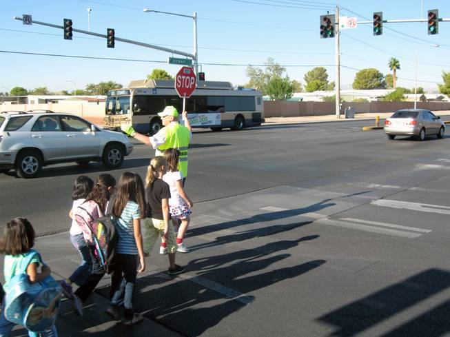 Crossing guard Paul Kmetz helps children across Christy Lane near Richard Rundle Elementary School on Tuesday.