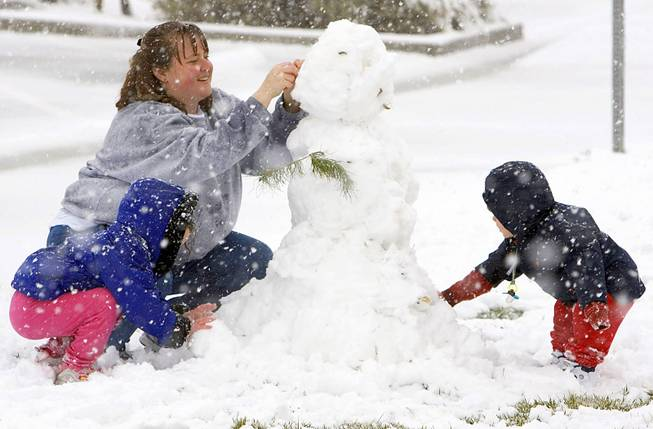 Janise Way builds a snowman with her daughter Jillian, left, and son Joey, right, during a snowstorm at Mountain Ridge Park on Friday, Jan. 7, 2004.