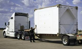 This undated image provided by the Waste Isolation Pilot Plant shows a New Mexico Department of Public Safety Motor Transportation Police Division officer inspecting the TRUPACT-III as it enters the state. The U.S. Department of Energy says this new shipping container used for moving radioactive tools and clothing known as transuranic waste arrived safely in New Mexico this week from South Carolina.
