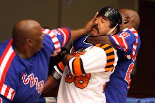 Veteran Bombers Ray Robles gets struck in the face by New York Chiefs big man Bernie Jackson as Chief teammate Greg Robertson attacks Robles from behind during their game.
